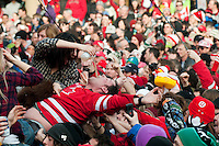 A man body surfs for a glug of beer as fans cheer wildly after team Canada won the Gold medal for hockey in the 2010 Olympic Winter Games in Whistler, BC Canada