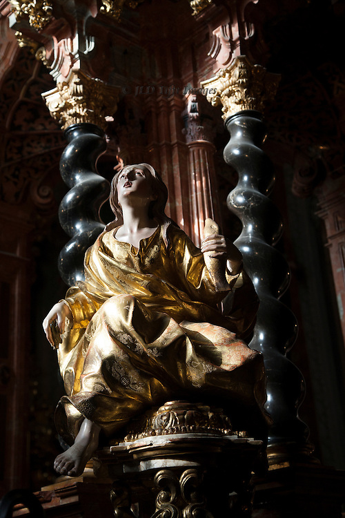 Wildly melodramatic Baroque statue of a woman in golden robes holding a golden fish and looking ecstatically upward in a demonstration of faith.  She is in the Sacristy of the Carthusian Charterhouse in Granada, Spain,  built between 1727 and 1764 by Luis de Arévalo and F. Manuel Vasquez