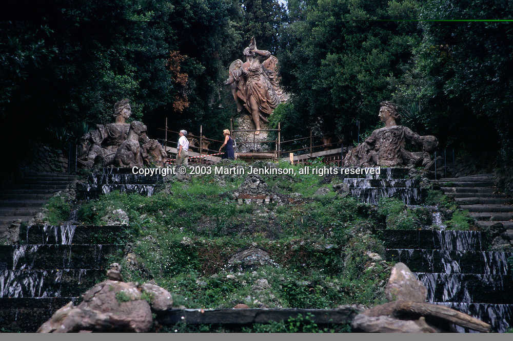 Statue of Fame and two female figures representing rivals Lucca and Florence in the 17th century baroque garden of the Villa Garzoni, Collodi, Tuscany, Italy.
