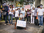 "02 JUNE 2013 - BANGKOK, THAILAND: A legless man leads a protest march through the Bangkok skywalk system. About 300 people wearing the Guy Fawkes mask popularized by the movie ""V for Vendetta"" and Anonymous, the hackers' group, marched through central Bangkok Sunday demanding the resignation of Prime Minister Yingluck Shinawatra. They claim that Yingluck is acting as a puppet for her brother, former Prime Minister Thaksin Shinawatra, who was deposed by a military coup in 2006 and now lives in exile in Dubai.      PHOTO BY JACK KURTZ"