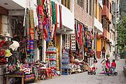 Souvenir shops and kids playing on walkway in Machu Picchu Pueblo, Peru.