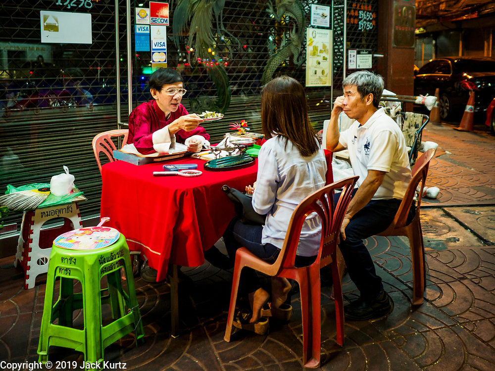 27 FEBRUARY 2019 - BANGKOK, THAILAND: A fortune teller predicts a woman's future on a street corner in Bangkok's Chinatown. Bangkok, a city of about 14 million, is famous for its raucous nightlife. But Bangkok's real nightlife is seen in its markets and street stalls, many of which are open through the night.        PHOTO BY JACK KURTZ