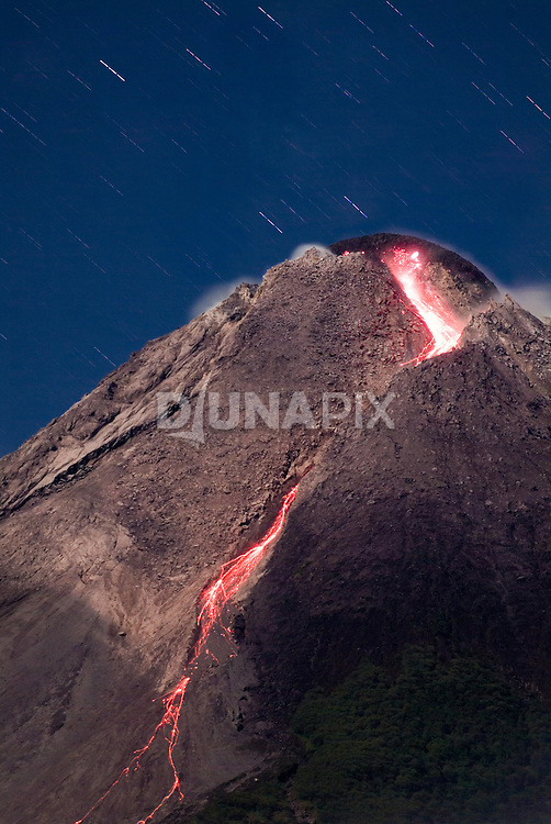 "FILE PHOTO: Lava pours from a bulging lava dome atop Mount Merapi on the evening of 12 May 2006. The emergent, visible dome is an unusual feature of Merapi--most ""plug dome"" or ""stratovolcanoes"" of this sort hide welling magma beneath a solid summit surface, forcing pressure to build until the volcano unleashes a catastrophic ""BOOM!"".  The longer the dome builds, the more likely it is to dislodge a flank of the peak and unleash a large eruption that tears through nearby villages. Home to 20,000 people, and one of the most active volcanoes in the ""ring of fire"", Merapi is rated as one of 15 of the world's most hazardous volcanoes, according to the International Association of Volcanology and Chemistry of the Earth."