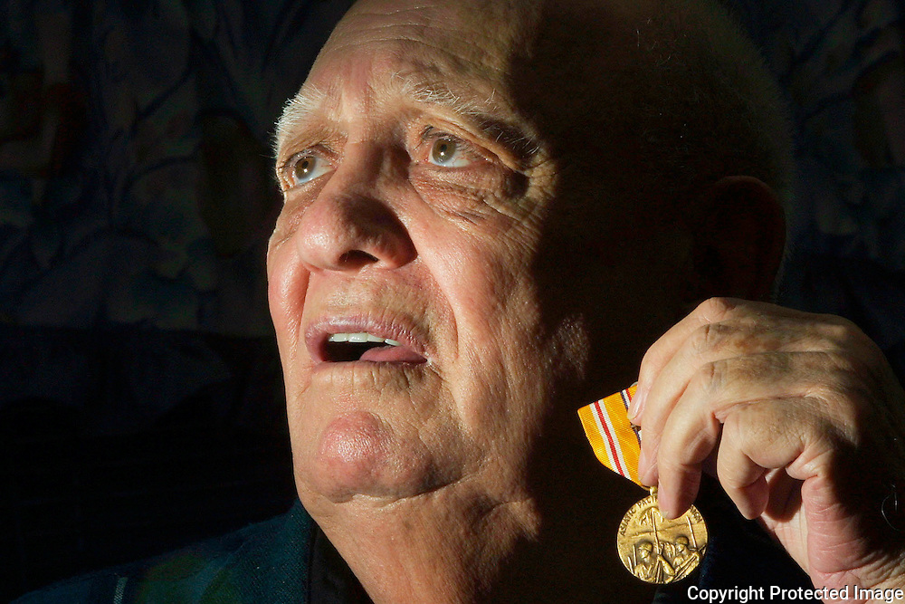 A World War II marine veteran proudly holds a medal he earned in the war.