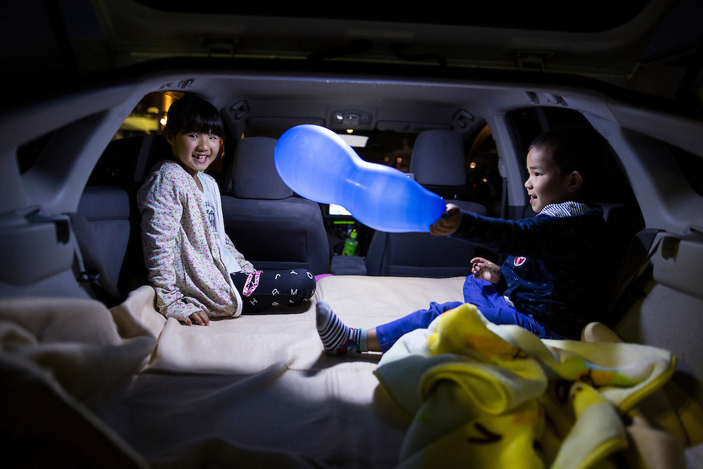 KUMAMOTO, JAPAN - APRIL 19: Misaki (9year old) and her younger brother Kose (6year old) playing inside their car before going to bed in the carpark of Mashiki Gymnasium evacuation center on April 19, 2016 in Mashiki, Kumamoto, Japan. Quake survivors face health threat, health experts says, 20 people diagnosed in Mashiki, one has died and 2 are in critical condition NHK reports.<br /> <br /> Photo: Richard Atrero de Guzman