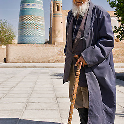 Old man with a stick, in front of Kalta minor minaret, Khiva, Uzbekistan, Asia