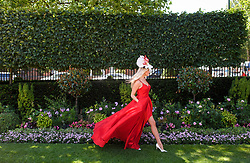 © Licensed to London News Pictures. 21/06/2018. London, UK. A woman poses for a photograph at Ladies Day at Royal Ascot at Ascot racecourse in Berkshire, on June 21, 2018. The 5 day showcase event, which is one of the highlights of the racing calendar, has been held at the famous Berkshire course since 1711 and tradition is a hallmark of the meeting. Top hats and tails remain compulsory in parts of the course. Photo credit: Ben Cawthra/LNP