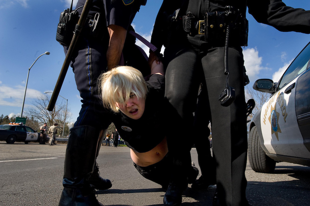 A protestor is arrested and dragged from a demonstration during a confrontation with police over education cuts in Davis near the University.