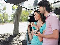 Couple drinking from thermos cups leaning in open tailgate of van half length