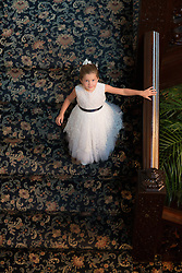 little girl in a formal dress walking down a staircase