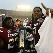 South Carolina Gamecocks defensive end Jadeveon Clowney (7) and South Carolina Gamecocks cornerback Victor Hampton (27) celebrate on the field after the NCAA Capital One Bowl football game between the South Carolina Gamecocks who represent the SEC and the Wisconsin Badgers who represent the Big 10 Conference, at the Florida Citrus Bowl on Wednesday, January 1, 2014 in Orlando, Florida.   South Carolina won the game 34-24. (AP Photo/Alex Menendez)