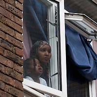 LONDON, ENGLAND - SEPTEMBER 11: A mother and daugher look outside the window where few alleged  anti islamist protesterors have been stoppd by Police on September 11, 2009 in London, England. Anti-fascist demonstrators and local Muslim youths have gathered to counter a threatened march by anti-Islamic right wing groups. (Photo by Marco Secchi/Getty Images)