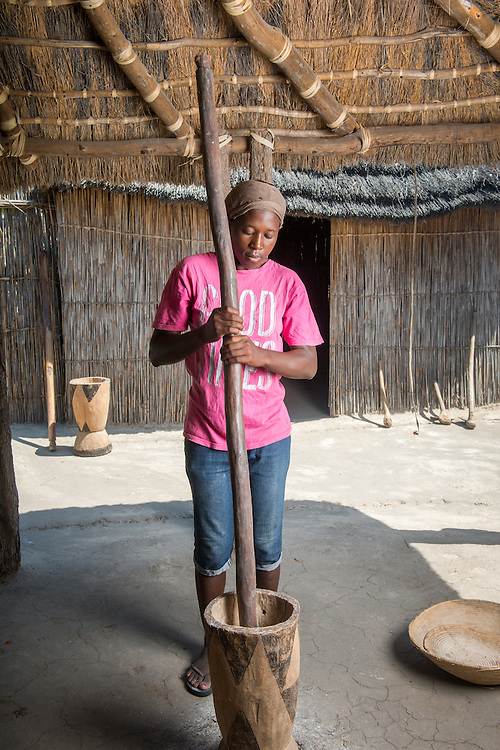 Maun, Botswana, Africa- African Woman using large mortar and pestle in Sexaxa Village