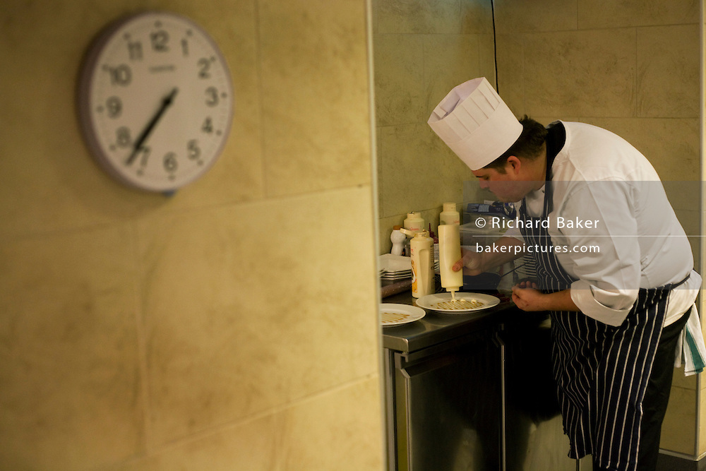 A chef puts finishing touches on deserts in the kitchens at the Vivre restaurant in Sofitel.