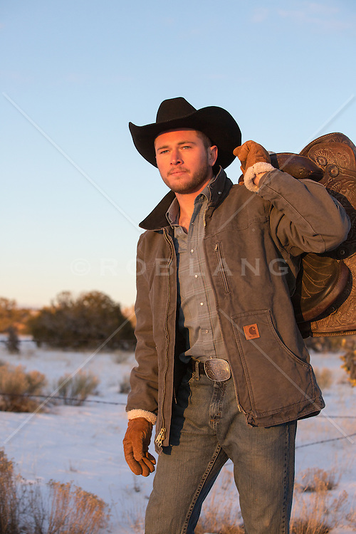 cowboy at sunset with a saddle over his shoulder
