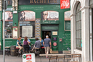 Dublin, Ireland--July 9, 2018. People sit down and enjoy a pint outside a pub in Ireland. A man is entering the doorway.