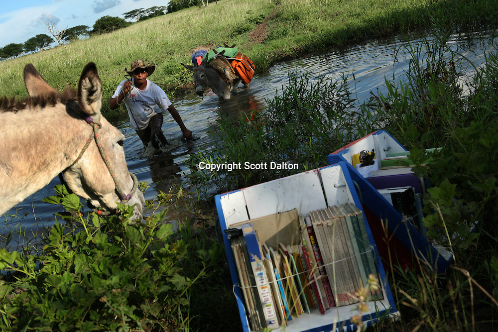 Luis Soriano, 36, leads a donkey through water in order to get his Biblioburro, or Donkey Library, from his hometown of La Gloria to El Brasil, in northern Colombia on Saturday, October 11, 2008. Mr. Soriano regularly takes long treks with his donkeys in tow in order to bring books to rural communities. (Photo/Scott Dalton)