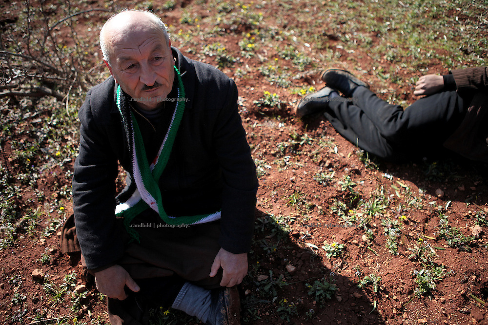 An old man hides in his olive orchard. On 22. February the syrian army attacked the village of Kureen, Province of Idlib, Syria. Kureen was among the first villages in the northwest of Syria controlled by the opposition. Some villagers and members of the defence units escaped to surrounding olive orchards, when the attack begun in the early morning. A majority of the inhabitants didn´t manage to escape. The heavy shelling lasts 7 houres. Soldiers searched all houses, burnt some of them down, loote shops, stole cars and furniture. About 60 motorcycles were burnt down. Tanks demolished several houses. 6 men were executed. One woman died as a result of an heart attack.