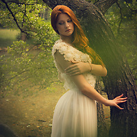 Female youth outdoors in spring wearing a white gown.