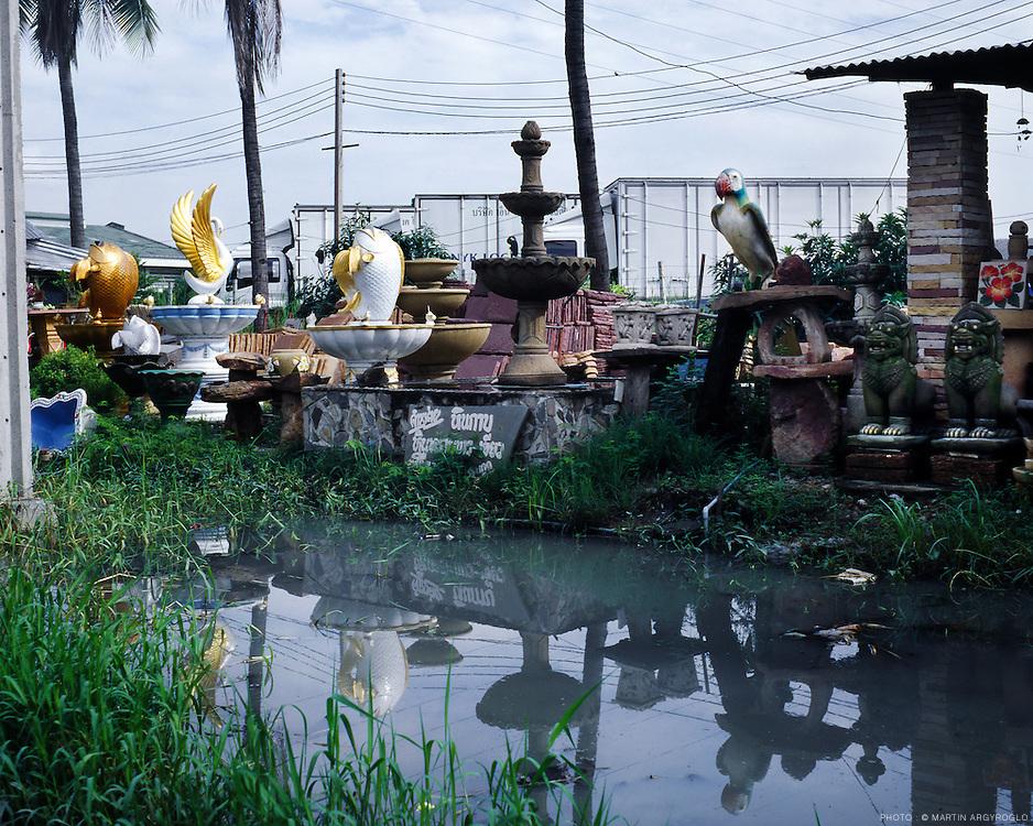 """Avec l'ouverture en 2006 du nouvel aéroport Suvarnabhumi de Bangkok, la zone traversée par l'axe reliant l'aéroport à la capitale est en passe de devenir un nouvel eldorado pour les investisseurs immobiliers, transformant cette zone périurbaine, en une zone d'implantation stratégique..Des nouveaux logements dont le standing est réévalué vers les standards occidentaux émergent ici ou là en marge de la route, reprenant en façade les fantasmes et les oripeaux du confort occidental, et l'appropriation de la modernité dans un contexte de développement accéléré..Espace - temporaire - de transition, cette route marque la confrontation sur un même territoire d'un habitat traditionnel issus d'une zone délaissée avec les nouveaux logements d'une zone nouvellement convoitée, destinée à une classe aisée et occidentalisée, formant une trame urbaine mixte..L'espace d'une route devient ici le paysage d'un champ d'expérience d'un processus rapide de métropolisation qui questionne, le temps d'une transition culturelle, le conditionnement du fantasme du mode de vie à l'occidental, par l'importation d'une modernité """"internationale"""".."""