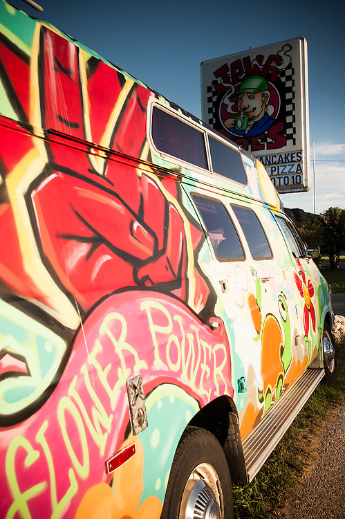 A camper van with painted mural reflecting the sentiments of the 1960s.
