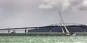 Yacht, Mischief Maker, sailing past the Auckland Harbour Bridge on a windy spring afternoon. Steam boat William C Daldy in background.