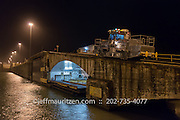 "A ""mule"" assists shipping vessels to transit the Gatun Locks in the Panama Canal at night."