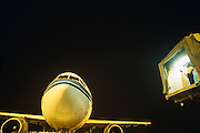 High up in the picture, two employees (one in traditional Arab clothes, the other in western dress) of Bahrain International Airport stand on the edge of a passenger 'air bridge' to oversee the departure of an airliner at Bahrain International Airport as it is pushed back by an unseen airport vehicle. It is night time and the ramp (or aircraft parking tarmac) is illuminated by yellow artificial light with the bridge itself, lit my overhead fluorescent tubes that give a blue-green tint above the mens' heads who watch the nose of a departing airliner. It is slowly taken backwards on its way to the runway take-off  position with its passengers on-board. We see only the fuselage, wings and part of its engine cowlings but not the undercarriage wheels, nor the ground itself. The men look as if they are floating in mid-air, being disembodied from the rest of the airfield's equipment.