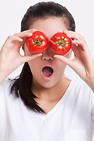 Young Asian woman covering her eyes with tomatoes against white background