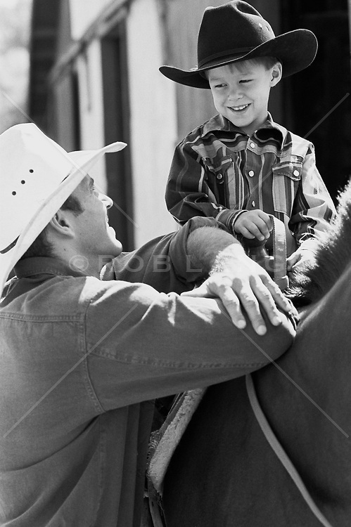 Cowboy talking to a boy on a horse