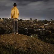 A young man looks over the slum of Korgocho in the capital Nairobi, Kenya.