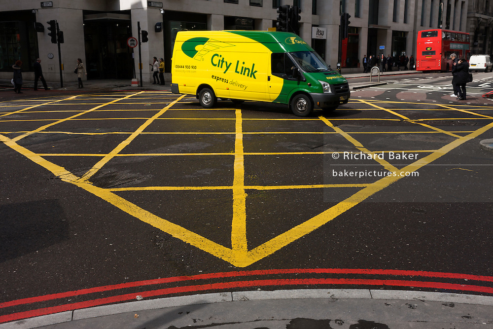 Bright yellow and green City Link delivery van drives mid-way over a yellow box junction grid in a City of London street.