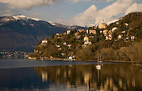 Ticino, Southern Switzerland. Lago Maggiore. Italian villages perched on the steep shoreline, reflected in the still waters of the lake.