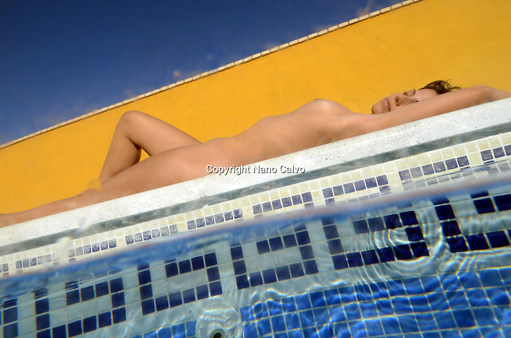 Attractive short haired woman sunbathing by the swimming pool