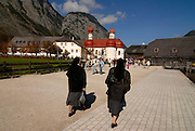 Nuns walking to the famous St. Bartholomä church on the  Königssee in the background the Watzman, Berchtesgadener land National park, Bavaria, Germany