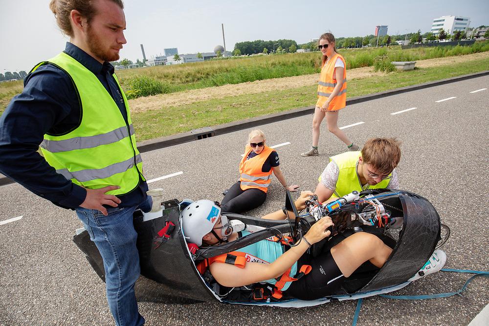 Lieke de Cock zit in de Velox, terwijl een techneut de ketting controleert. Op een weg in Delft worden de eerste meters afgelegd met de nieuwe recordfiets, de VeloX 8. In september wil het Human Power Team Delft en Amsterdam, dat bestaat uit studenten van de TU Delft en de VU Amsterdam, tijdens de World Human Powered Speed Challenge in Nevada een poging doen het wereldrecord snelfietsen voor vrouwen te verbreken met de VeloX 8, een gestroomlijnde ligfiets. Het record is met 121,81 km/h sinds 2010 in handen van de Francaise Barbara Buatois. De Canadees Todd Reichert is de snelste man met 144,17 km/h sinds 2016.<br /> <br /> At a road in Delft the team tests the VeloX 8 for the first time. With the VeloX 8, a special recumbent bike, the Human Power Team Delft and Amsterdam, consisting of students of the TU Delft and the VU Amsterdam, also wants to set a new woman's world record cycling in September at the World Human Powered Speed Challenge in Nevada. The current speed record is 121,81 km/h, set in 2010 by Barbara Buatois. The fastest man is Todd Reichert with 144,17 km/h.