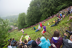 © Licensed to London News Pictures 26/05/2018, brockworth, Gloucester, UK. The annual cheese rolling race held at Coopers Hill, Brockworth outside Gloucester. Competitors race down the extremly steep slippery hill chasing a double Gloucester cheese, the winner of each race recieves the cheese as thier prize. Pictured here : Competitors race down the hill after the cheese -  Photo Credit : Stephen Shepherd/LNP