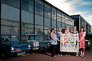 Lesley Thornton and the rest of her stitching group pose with the Linwood / Hillman Imp panel for the Great Tapestry of Scotland project. Photographed at the site of the old factory in Linwood with a small group of Hillman Imp enthusiasts<br /> www.scotlandstapestry.com<br /> <br /> pictures by Alex Hewitt