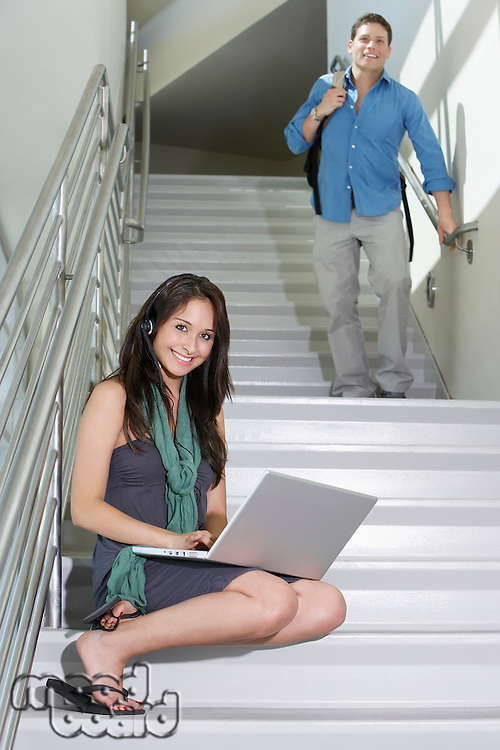 Female student using laptop on stairs, young man in background