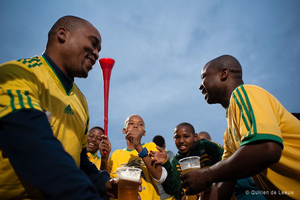 Zuid Afrikaanse voetbalsupporters vieren een doelpunt tijdens een wedstrijd van de Bafana's.