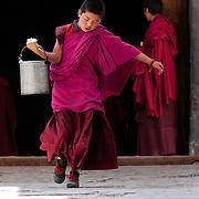 Novice monk carrying water at Labrang Monastery, Xiahe, Gansu, China