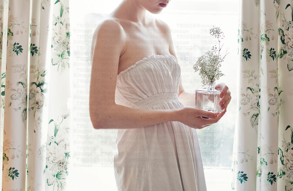 Slender young woman wearing a white dress with pale skin holding baby's breath flowers, against a window with rain drops on it surrounded by floral curtains.