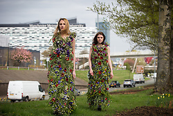 "© Licensed to London News Pictures . FREE TO USE PHOTOGRAPH . No syndication , onward sale of transfer permitted . 16/04/2015 . Manchester , UK . As England bathes in warm Spring sunshine , models Danielle Bowers (21 from Liverpool) and Ailyce Ridings (correct, 20, from Manchester) model wild flower dresses on Manchester's Princess Parkway (A5103) to mark Grow Wild's England flagship project , "" Tale of Two Cities "" , a joint venture between rival cities Manchester and Liverpool , which will see heavily travelled urban landscapes transformed in to stunning wildflower meadows . Photo credit : Joel Goodman/LNP"