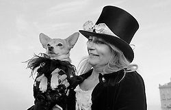 © Licensed to London News Pictures.01/11/15<br /> Whitby, UK. <br /> <br /> A woman wearing gothic clothing stands with her dog during the Whitby Goth weekend in Whitby, North Yorkshire. The event began in 1994 to celebrate goth culture and music and takes place twice each year. <br /> Thousands of extravagantly dressed people attend the popular event wearing Steampunk, Cybergoth, Romanticism, Victoriana and other clothing as they take part in the celebration of Goth culture. <br /> <br /> Note to Editors - Picture shot on Kodak Tri X 400ISO film.<br /> Photo credit : Ian Forsyth/LNP