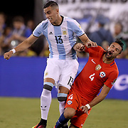 EAST RUTHERFORD, NEW JERSEY - JUNE 26:   Mauricio Isla #4 of Chile receives a hard challenge from Ramiro Funes Mori #13 of Argentina during the Argentina Vs Chile Final match of the Copa America Centenario USA 2016 Tournament at MetLife Stadium on June 26, 2016 in East Rutherford, New Jersey. (Photo by Tim Clayton/Corbis via Getty Images)