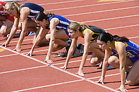Female athletes in starting blocks, ready to run