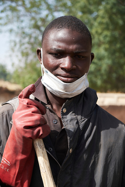 Babaye Abdou, 18 years old takes part in a Cartias community activity program for teenage boys and men collecting rubbish in the town of Diffa, Niger on February 12, 2016. 65 men without other means of employment engage in the program collecting rubbish in the streets of various neighbourhoods of Diffa. They participate 10 times per month and are paid 1300 francs (approx. $2) each time. Seen as vulnerable group, especially young men between the age of 14-35 who are susceptible to joining Boko Haram because of no means of earning an income in Diffa, the purpose of the program is the give these men some means of earning money. Many youth after school in the past purchased motorbikes and worked as taxi drivers in the city. With the military banning this in late 2015 because of the frequency of attacks by Boko Haram on motorbikes, approximately 600 who worked in this profession are without jobs. The Caritas staff leading the program undertake awareness campaigns teaching young men about all the damaging effects of the current crisis in the region triggered by Boko Haram.  <br /> <br /> 'I heard about the program in my neighbourhood through friends of mine that were involved and they introduced me to the organisers. It's the first time I have participated and I needed the work. Before I had a job making bricks but with an injury I can't do that anymore so this gives me some income.'