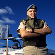 Dallaire Testifies Before UN International Criminal Tribunal for Rwanda<br />  Seen in this December 1994 image, then-Major General Romeo Dallaire poses in front of a UN jeep bearing the flag that accompanied Dallaire during his tour of duty as the leader of the UN mission in Rwanda. Testifying before the United Nations International Criminal Tribunal for Rwanda on January 20, 2004, Dallaire, said he warned UN headquarters three months before the genocide about the stockpiling of arms.   &copy; Christopher J. Morris/Corbis