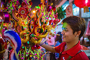 "09 FEBRUARY 2013 - BANGKOK, THAILAND:  A Chinese toy vendor sells New Year's trinkets on Yaowarat Road in Chinatown in Bangkok. Bangkok has a large Chinese emigrant population, most of whom settled in Thailand in the 18th and 19th centuries. Chinese, or Lunar, New Year is celebrated with fireworks and parades in Chinese communities throughout Thailand. The coming year will be the ""Year of the Snake"" in the Chinese zodiac.   PHOTO BY JACK KURTZ"