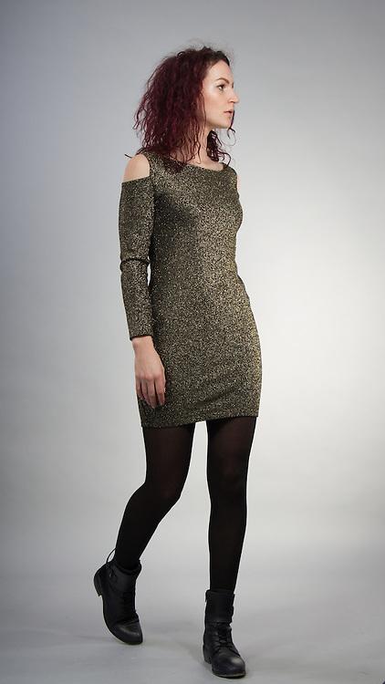 Female model posing in green dress.
